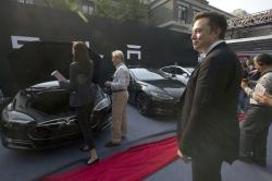 In this April 22, 2014, file photo. Tesla Motors CEO Elon Musk, right, looks on as a set of Tesla Model S sedans are delivered to its first customers in China at an event in Beijing