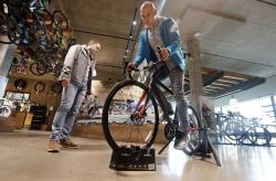 "In this Nov. 13, 2018, photo Vitalii Myroshnychenko, right, test rides a bike atop a stand as Denis Rybalchenko looks on in REI Co-op's flagship store in Seattle. The usual advice is ""buy experiences, not things."" But that requires a deeper dive. A bicycle can provide an experience, and a new camera can preserve one. So buy experiences, especially with other people, but also think about buying material things that allow you to have experiences or enhance them."