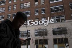 In this file photo dated Monday, Dec. 17, 2018, a man using a mobile phone walks past Google offices in New York, USA
