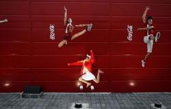 In this Aug. 20, 2008 file photo, a young girl mimics the pose of a Chinese Olympic athletes depicted in Coca-Cola advertising, at the Olympic green in Beijing