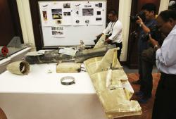 In this June 19, 2018 file photo, photographers take pictures of what U.A.E. officials described as an Iranian Qasef drone captured on the battlefield in Yemen during a news conference in Abu Dhabi, United Arab Emirates