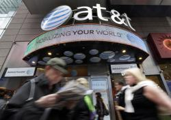 In this Oct. 21, 2014 file photo, people pass an AT&T store in New York's Times Square