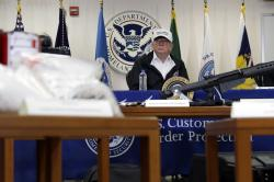 With illegal drugs and weapons displayed in the foreground, President Donald Trump speaks at a roundtable on immigration and border security at U.S. Border Patrol McAllen Station, during a visit to the southern border.