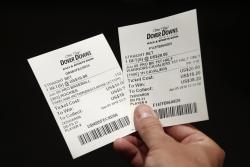 In this June 5, 2018, file photo, John Celatka displays a pair of receipts for bets he placed on an MLB baseball game and an NBA basketball game, inside the Race and Sports Book at Dover Downs Hotel and Casino in Dover, Del.
