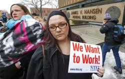 IRS worker Christine Helquist looks on during a federal workers protest rally at the Federal Building.