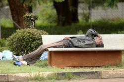 In this Jan. 9, 2019, photo, a man lies on a bench outside a government hospital after being turned away during the doctors strike at Parirenyatwa Hospital, in Harare, Zimbabwe.