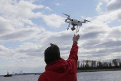 In this April 29, 2018, file photo, a drone operator helps to retrieve a drone after photographing over Hart Island in New York