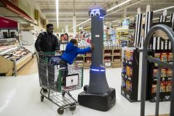 William Rucker and his grandson Justice, 4, say hello to a robot named Marty as it cleans the floors at a Giant grocery store in Harrisburg, Pa., Tuesday, Jan. 15, 2019