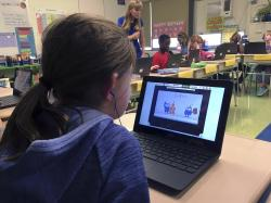 In this Sept. 20, 2018 photo, fifth grade student Ashlynn De Filippis, left, works math problems on the DreamBox system as teacher Heather Dalton, center rear, works with other students in class at Charles Barnum Elementary School in Groton, Conn.
