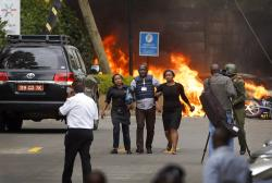 Security forces help civilians flee the scene as cars burn behind, at a hotel complex in Nairobi, Kenya.
