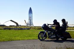In this Jan. 12, 2019 file photo, a motorcyclist rides near the SpaceX prototype Starship hopper at the Boca Chica Beach site in Texas