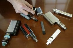 In this April 10, 2018, file photo, a high school principal displays vaping devices that were confiscated from students in such places as restrooms or hallways at the school in Massachusetts