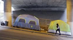 In this March 8, 2017 file photo, a person walks up a hill next to tents lined up beneath a highway and adjacent to downtown Seattle. Microsoft pledged $500 million to address homelessness and develop affordable housing in response to the Seattle region's widening affordability gap