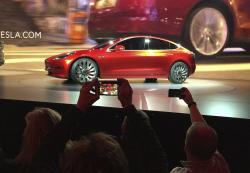 In this March 31, 2016 file photo, Tesla Motors unveils the new lower-priced Model 3 sedan at the Tesla Motors design studio in Hawthorne, Calif.