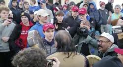 """A teenager wearing a """"Make America Great Again"""" hat, center left, stands in front of an elderly Native American singing and playing a drum in Washington."""