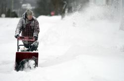 John Ott clears snow on Madison Avenue in Pittsfield, Mass.