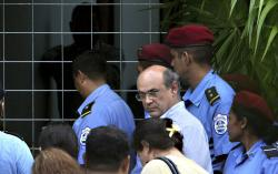 In this Oct. 11, 2008 file photo, journalist Carlos Fernando Chamorro, who runs the Communication Research Center, Cinco, is surrounded by the police as a search warrant is carried out at Cinco's facilities in Managua, Nicaragua