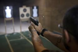 In this Jan. 10, 2019 photo, Rildo Anjos, owner of the Calibre 12 gun club, fires his pistol during a practice session at the club in Sao Goncalo, Brazil