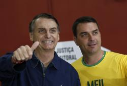 In this Oct. 7, 2018 file photo, then-presidential frontrunner Jair Bolsonaro, left, accompanied by his son Flavio Bolsonaro, arrives to vote in the general election in Rio de Janeiro, Brazil