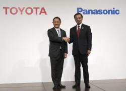 In this Dec. 13, 2017, file photo, Toyota Motor Corporation President Akio Toyoda, left, and Panasonic Corporation President Kazuhiro Tsuga, right, pose for photographers after a joint press conference in Tokyo