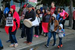 Parents arrive with their children to Evelyn Thurman Gratts Elementary School as people rally in support of Los Angeles school teachers Tuesday, Jan. 22, 2019, in Los Angeles.