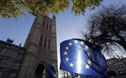 The sun shines through European Union flags tied to railings outside parliament in London, Tuesday, Jan. 22, 2019