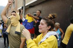 Anti-government protesters show support for an apparent mutiny by a national guard unit in the Cotiza neighborhood of Caracas, Venezuela, Monday, Jan. 21, 2019