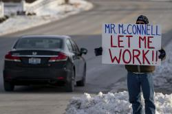 Furloughed EPA worker Jeff Herrema holds a sign outside the offices of U.S. Senator Mitch McConnell, in Park Hills, Ky., Tuesday, Jan 22, 2019
