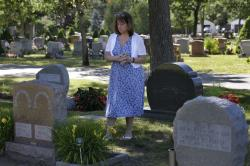 Cheryl Juaire, of Marlborough, Mass., stands at her son's grave, in Chelmsford, Mass., on Tuesday, June 19, 2018