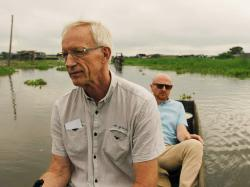 Director Mads Brügger is seen in a boat, seated behind Göran Björkdahl, in the documentary 'Cold Case Hammarskjöld'
