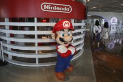In this June 19, 2018, photo, visitors walk around a figure of Super Mario of Nintendo at Panasonic center in Tokyo