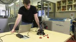 In this image made from a Feb. 1, 2019, video, Robert Kwiatkowski, a graduate student at Columbia University, demonstrates a robotic arm picking up a red ball and dropping it in a cup at the school in New York