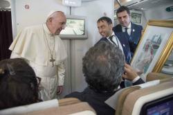 Pope Francis receives a gift from a journalist during his flight from Abu Dhabi to Rome.