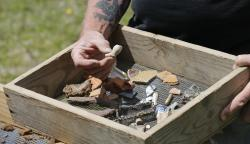 In this April 10, 2018, file photo, Historic Jamestowne staff archaeologist Lee McBee displays artifacts as he talks with visitors at the dig site of the Angelo slave house in Jamestown, Va.