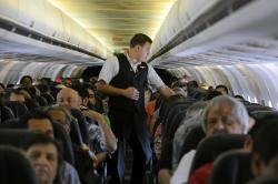 In this May 9, 2013, file photo, Allegiant Air flight attendant Chris Killian prepares his passengers for the Laredo, Tex, bound flight before it pushes back from the terminal at McCarran International Airport in Las Vegas