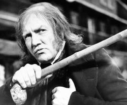 "British actor Albert Finney waves his cane while playing the title role in ""Scrooge"" in 1970."