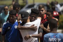 Friends grieve during the funeral of the young soccer player Arthur Vinicius, one of the victims of a fire at a Brazilian soccer academy, in Volta Redonda, Brazil, Saturday, Feb. 9, 2019.