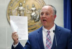 North Carolina House Democratic leader Darren Jackson holds up a copy of HB 186.