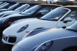 In this Sunday, Feb. 3, 2019, photograph, a long row of unsold 2019 911 Carrera GTS cabriolets sits at a Porsche dealership in Littleton, Colo.