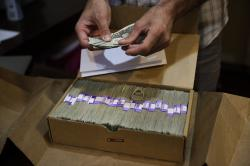 In this June 27, 2017 file photo, the proprietor of a medical marijuana dispensary prepares his monthly tax payment, over $40,000 in cash, at his Los Angeles store