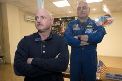 In this March 26, 2015 file photo, U.S. astronaut Scott Kelly, right, crew member of the mission to the International Space Station, stands behind glass in a quarantine room, behind his brother, Mark Kelly, also an astronaut, after a news conference in the Russian-leased Baikonur, Kazakhstan cosmodrome