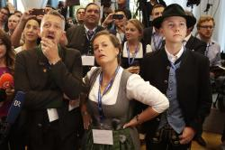 In this Sunday, Oct. 14, 2018 file photo, supporter of the Christian Social Union, CSU, react in the state parliament in Munich, Germany, after the polling stations for the Bavarian state elections have closed