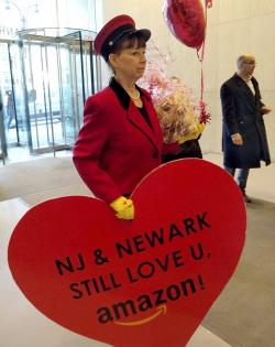 """In this Feb. 14, 2019 photo provided by Newark Alliance, Laurie Ross, an actor with the event planners at Life 'O the Party, holds a message reading """"NJ & Newark Still Love U, Amazon!"""" while arriving at an Amazon office in New York"""