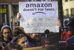 In this Nov. 14, 2018 file photo, protesters hold up anti-Amazon signs during a coalition rally and press conference of elected officials, community organizations and unions opposing Amazon headquarters getting subsidies to locate in Long Island City, in New York