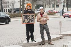 Local D.C. artist Mike Green, left, looks on as Adam Eidinger, with Radical Matriarchy, protests topless outside the National Gallery of Art on Thursday, Feb. 14, 2019 in Washington.