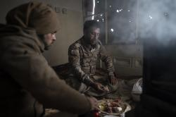 U.S.-backed Syrian Democratic Forces (SDF) fighters eat in a building as the fight against Islamic State militants continues in the village of Baghouz, Syria, Sunday, Feb. 17, 2019.