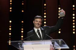 Director Francois Ozon holds aloft the Silver Bear grand jury prize for the film 'By the Grace of God' onstage at the award ceremony of the 2019 Berlinale Film Festival in Berlin, Germany, Saturday, Feb. 16, 2019. (AP Photo/Markus Schreiber)