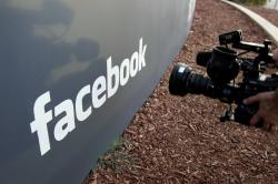 In this May 18, 2012, file photo a television photographer shoots the sign outside of Facebook headquarters in Menlo Park, Calif.