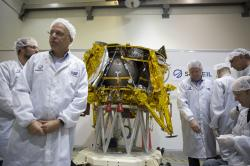 """In this Monday, Dec. 17, 2018 file photo, technicians stand next to the SpaceIL lunar module, an unmanned spacecraft, is on display in a special """"clean room"""" where the space craft is being developed, during a press tour of their facility near Tel Aviv, Israel"""