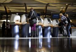 Passengers check in for Delta Air Lines flights at kiosks at Hartsfield-Jackson Atlanta International Airport in Atlanta.